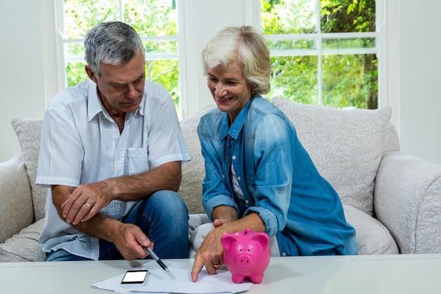 Glückliche ältere paare, die zu hause einsparungen berechnen