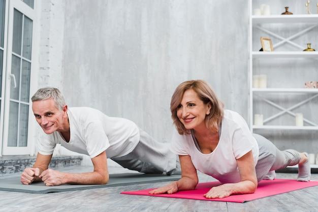 Glückliche ältere paare, die zu hause yogaübung tun