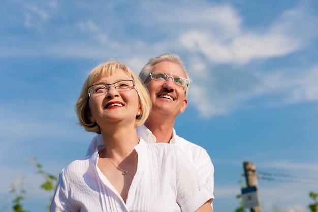 Glückliche ältere paare, die zum blauen himmel schauen
