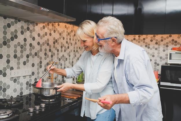 Glückliche ältere paare, die zusammen gesundes lebensmittel im küchenraum kochen