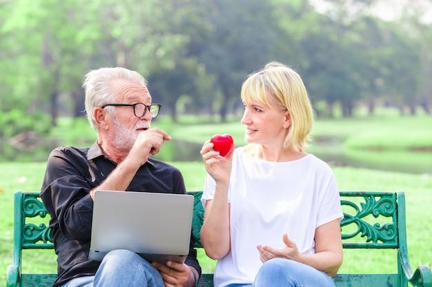 Glückliche ältere paare im park, der herz im liebesvalentinstagkonzept hält