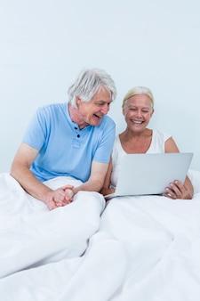 Glückliche ältere paare unter verwendung des laptops beim sitzen auf bett