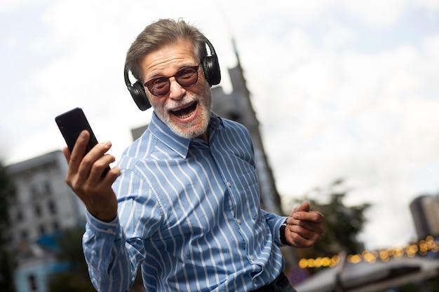 Glückliche ältere person, die musik hört