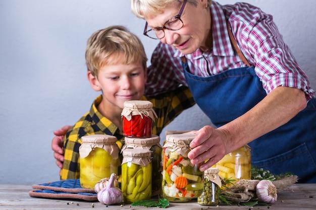 Glückliche ältere reife frau, großmutter und kleiner junge, enkel, der in handgläsern mit hausgemachten konservierten und fermentierten lebensmitteln, eingelegtem und mariniertem gemüse hält. ernteerhalt, familienzeit