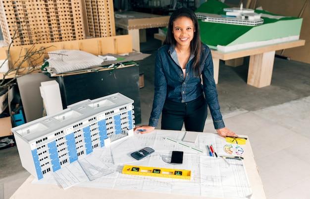 Glückliche african-americandame, die nahes modell des gebäudes auf tabelle steht