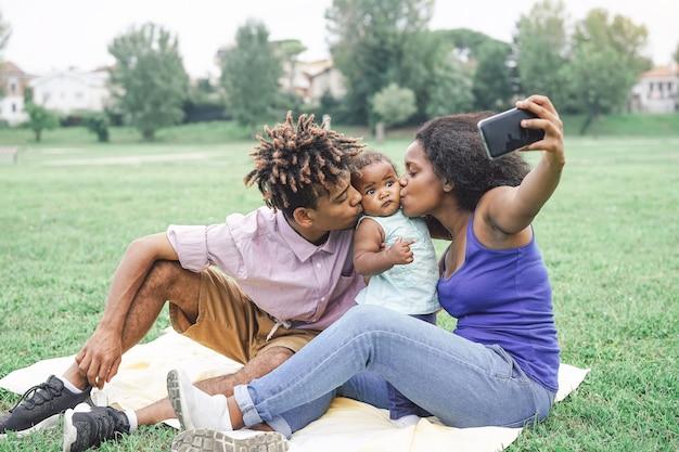 Glückliche afrikanische familie, die ein selfie mit intelligenter handykamera in einem allgemeinen park im freien nimmt