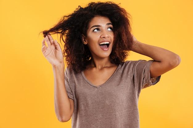 Glückliche afrikanische frau, die ihr haar berührt und nach oben schaut