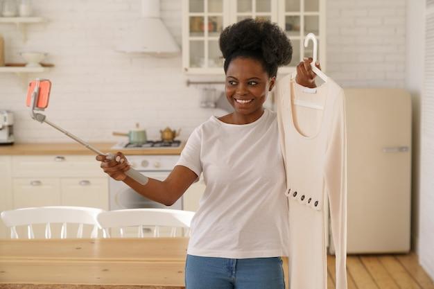 Glückliche afrikanische frau, die mode-sommerkleid durch smartphone auf stativ online im live-streaming zeigt