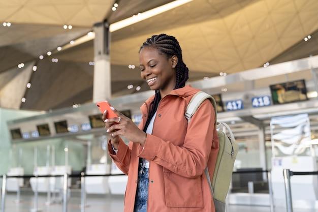 Glückliche afrikanische frau, die nach ihrem flug am flughafen ihr telefon überprüft