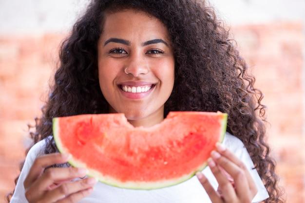 Glückliche afrikanische frau in der küche und halten scheibe einer wassermelone