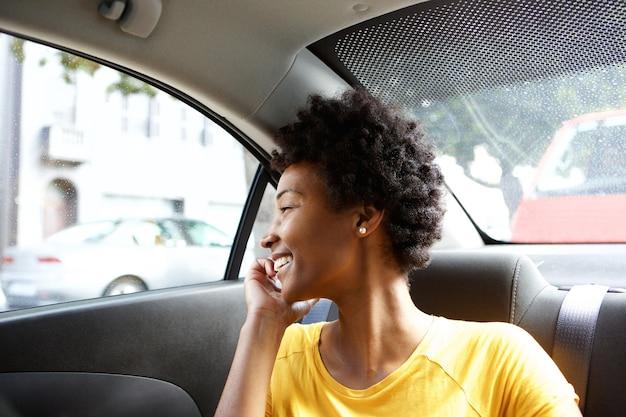 Glückliche afrikanische frau in einem auto, das auf mobiltelefon spricht