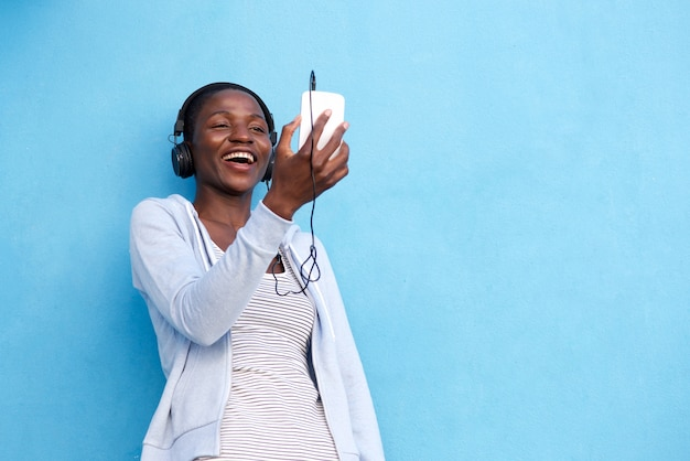 Glückliche afrikanische frau mit intelligentem telefon und kopfhörern