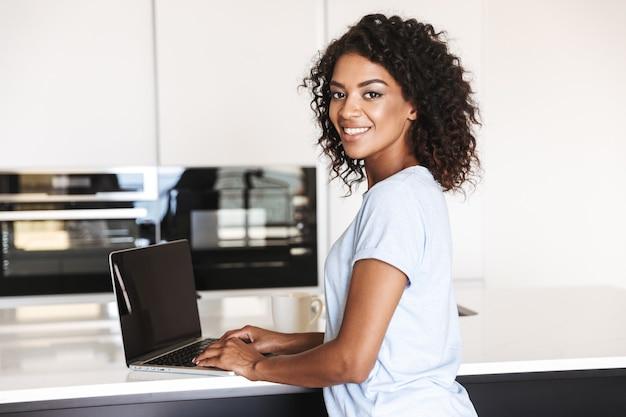 Glückliche afrikanische frau mit laptop-computer