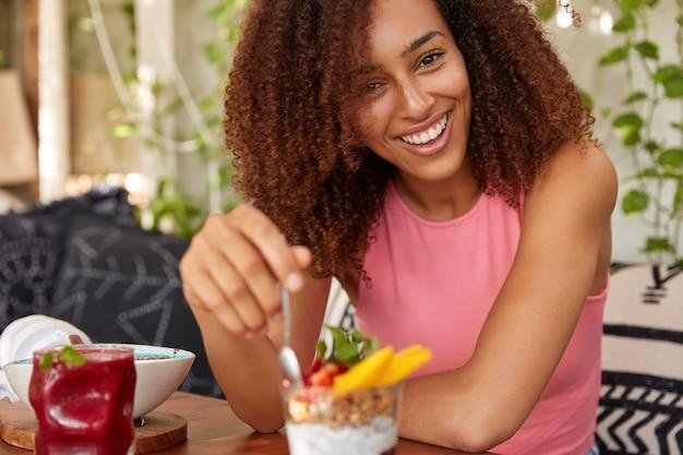 Glückliche afrikanische frau mit lockigem haar