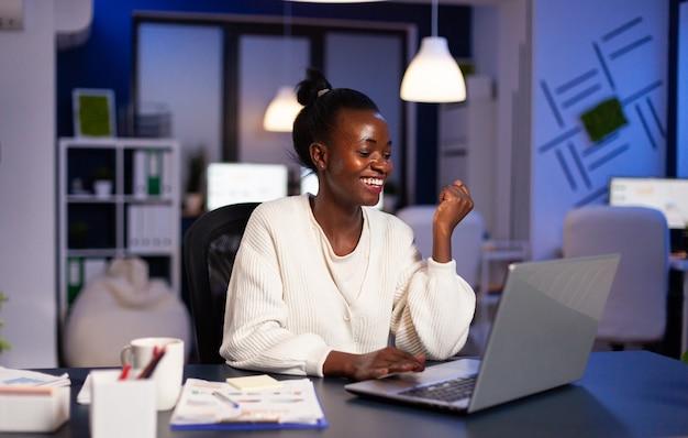 Glückliche afrikanische frau, nachdem sie e-mails mit guten nachrichten gelesen hat, die spät in der nacht arbeiten?