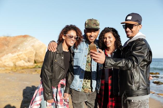 Glückliche afrikanische freunde, die gehen, machen selfie per handy.