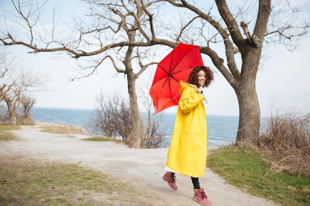Glückliche afrikanische lockige junge dame, die gelben mantel hält regenschirm trägt
