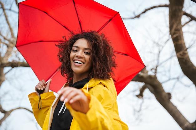 Glückliche afrikanische lockige junge dame, die gelben mantel mit regenschirm trägt.