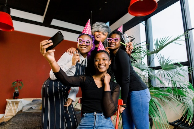 Glückliche afrikanische mädchen feiern geburtstag in hüten und fotografieren auf einem smartphone