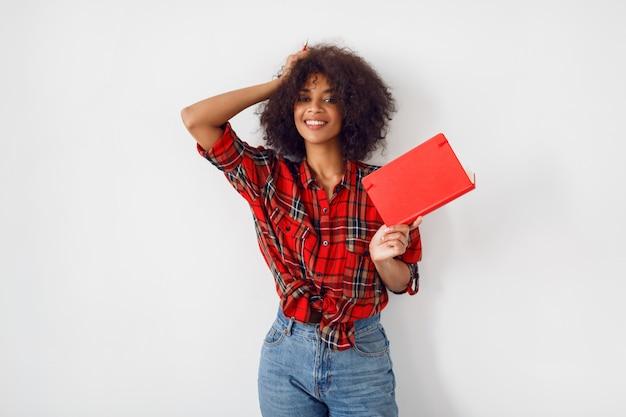 Glückliche afrikanische studentin mit buch, das innen über weißer wand aufwirft. tragen eines rot karierten hemdes. blaue jeans.