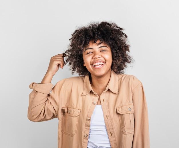 Glückliche afroamerikanerfrau, die mit ihrem haar spielt