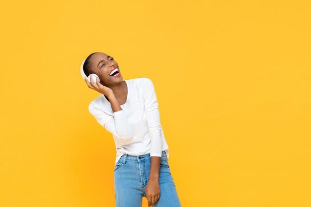 Glückliche afroamerikanerfrau lachend, während musik auf drahtlosem kopfhörer lokalisiert auf gelber wand hört