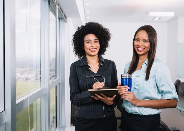 Glückliche afroamerikanerfrauen mit dokumenten und thermosflasche nahe fenster im büro