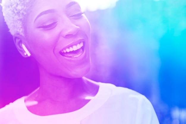 Glückliche afroamerikanerin, die mit drahtlosen kopfhörern musik hört
