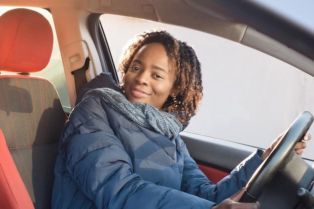 Glückliche afroamerikanerin in einem mantel, die ihr auto fährt