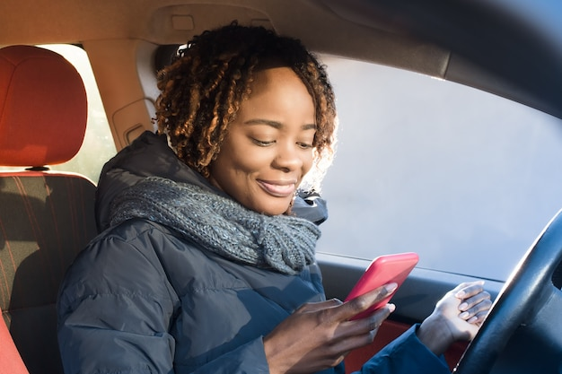 Glückliche afroamerikanerin in einem mantel, die ihr telefon in ihrem auto überprüft