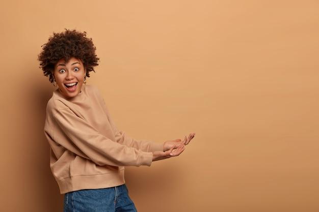 Glückliche afroamerikanerin steht seitwärts, gibt vor, etwas von unten zu halten, steht mit erhobenen handflächen, trägt unsichtbares objekt