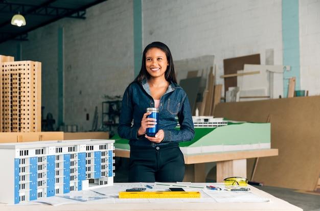 Glückliche afroamerikanische dame mit der thermosflasche, die nahe modell des gebäudes steht