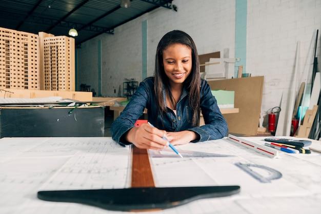 Glückliche afroamerikanische dame mit großem machthaber und stift bei tisch