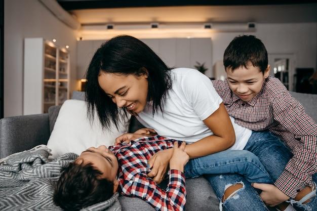 Glückliche afroamerikanische familienmutter und zwei söhne, die herumalbern und spaß zu hause zusammen haben. hochwertiges foto