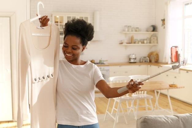 Glückliche afroamerikanische frau, die mode-sommerkleid durch handy auf stativ online zu hause zeigt