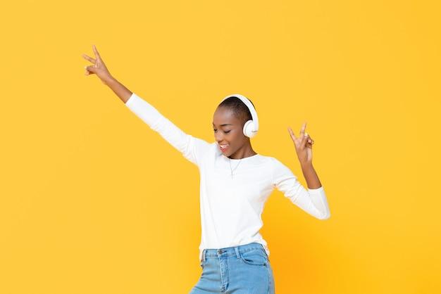 Glückliche afroamerikanische frau, die musik auf drahtlosem kopfhörer mit den händen oben lokalisiert auf gelber wand hört