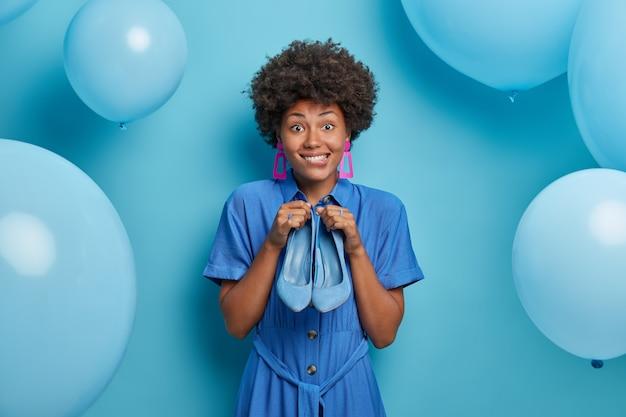 Glückliche afroamerikanische frau im blauen kleid, hält schöne schuhe, kleider für besonderen anlass, bereitet sich auf abend date vor. frohe geburtstagsfrau bekommt schuhe als geschenk, posiert in der nähe von blauen luftballons