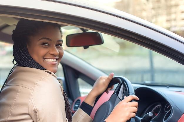 Glückliche afroamerikanische frau in einem autofahren, herbst-winter.