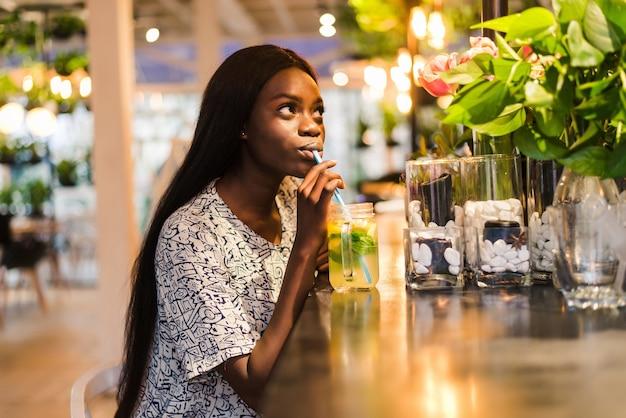Glückliche afroamerikanische frau mit glas natürlicher limonade im café. detox-getränk