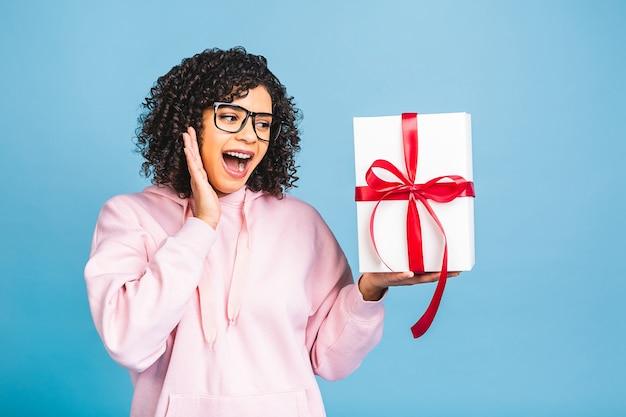 Glückliche afroamerikanische lockige dame im lässigen lachen, während geschenkgeschenkbox lokalisiert über blauem hintergrund gehalten wird.