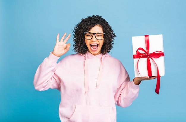 Glückliche afroamerikanische lockige dame im lässigen lachen, während geschenkgeschenkbox lokalisiert über blauem hintergrund hält.