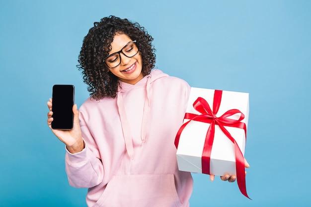 Glückliche afroamerikanische lockige dame in lässigem lachen, während geschenk lokal über blauem hintergrund gehalten. telefon benutzen.
