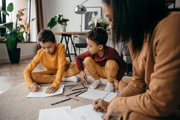 Glückliche afroamerikanische mutter, die ihre söhne lehrt, mit bleistift-muttertagskonzept zu zeichnen