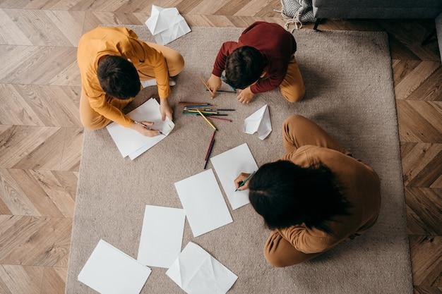 Glückliche afroamerikanische mutter, die ihren söhnen beibringt, mit bleistiften zu zeichnen. muttertagskonzept. draufsicht. hochwertiges foto