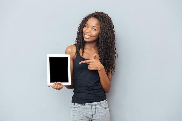 Glückliche afrofrau, die leeren tablet-computer über grauer wand zeigt