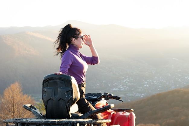Glückliche aktive fahrerin, die bei sonnenuntergang extremes fahren auf einem atv-quad-motorrad in den herbstbergen genießt.