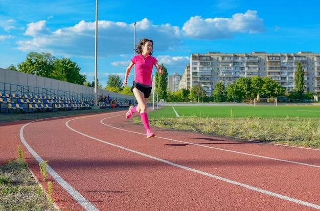 Glückliche aktive frau, die auf bahn rüttelt, auf stadion, sport und eignung läuft und ausarbeitet