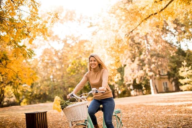 Glückliche aktive frau, die fahrrad im goldenen herbstpark fährt