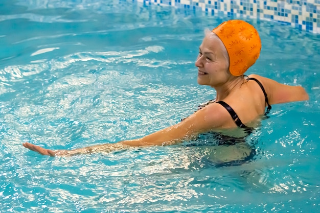 Glückliche aktive seniorin, die fitnesskurse in aqua-aerobic im pool nimmt?