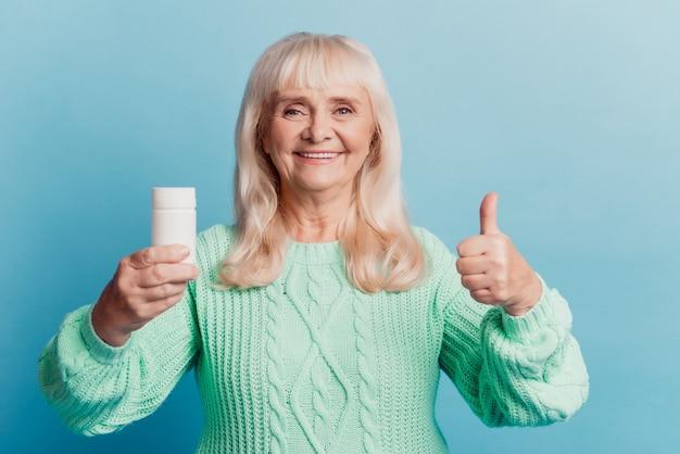 Glückliche alte dame hält pillenglas zeigen feine geste isoliert auf blauem hintergrund
